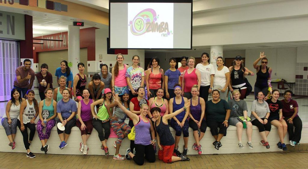 Zumba participants pose onstage.